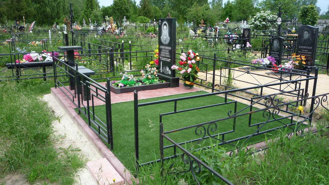 Гранитный памятник, тротуарная плитка и трава